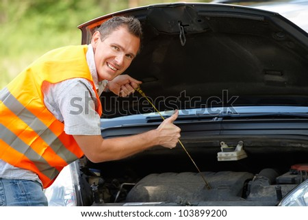 Man checking level of oil on a car engine dipstick