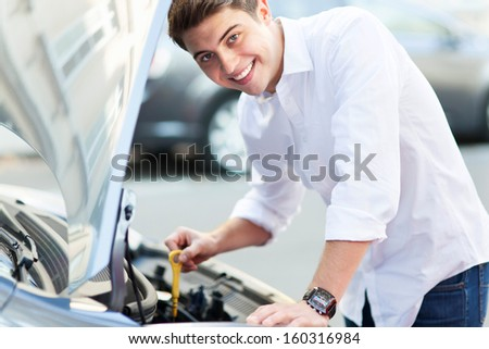 Man checking oil level in car