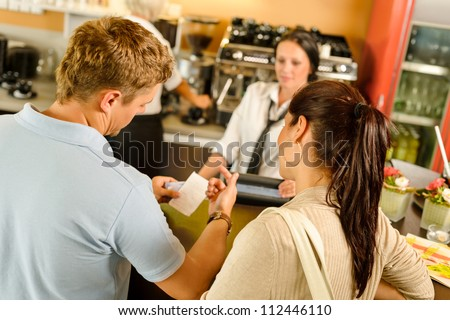 Man checking receipt at cafe restaurant payment waitress couple bar - stock photo