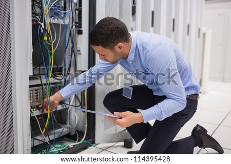 Man checking tablet pc as he is plugging cables into server in data center - stock photo