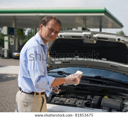 Man checking the oil levels in his car at a gas station, using a dipstick - stock photo