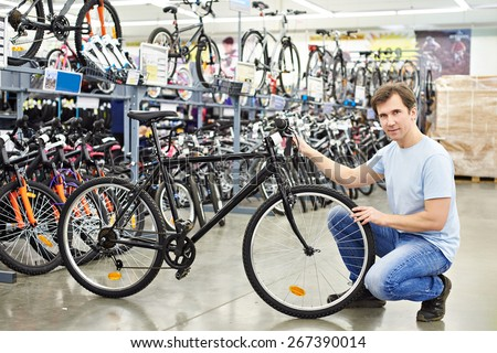 Man checks a bike before buying in the sports shop - stock photo
