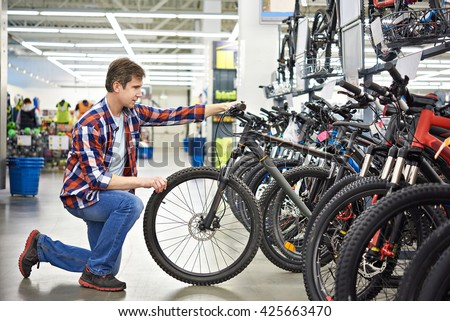 Man checks bike before buying in sports shop - stock photo