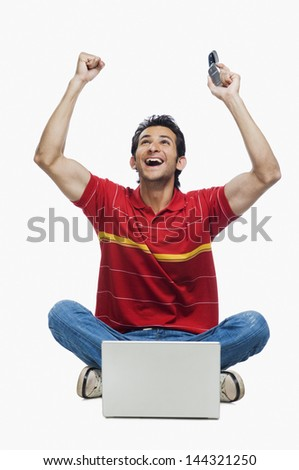 Man cheering in front of a laptop and holding a mobile phone - stock photo