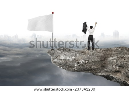 man cheering on cliff with blank white flag and gray cloudy cityscape background