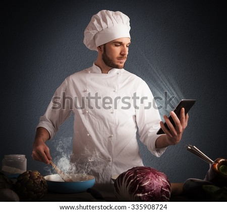 Man chef cooking while reading on tablet - stock photo