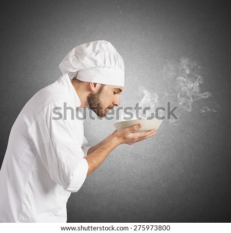 Man chef smelling the aroma of his dish - stock photo