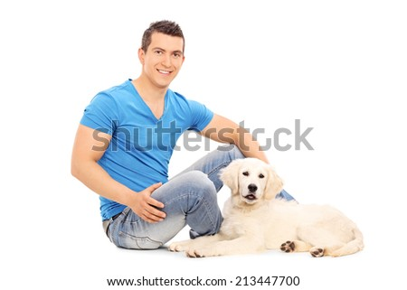 Man chilling out with his puppy seated on floor isolated on white background - stock photo