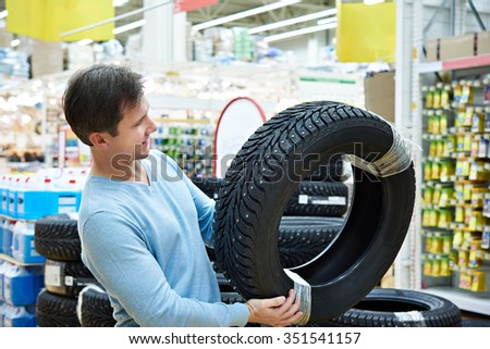 Man chooses a winter studded tires for a car in a supermarket