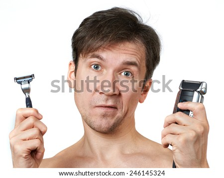 Man chooses between two razors - stock photo