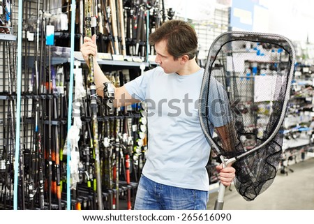 Man chooses fishing rod and landing net in the sports shop