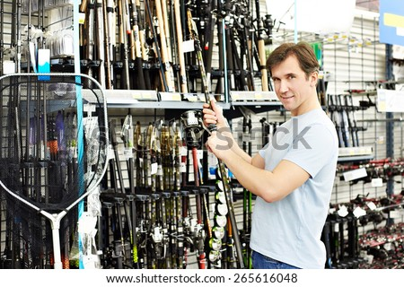 Man chooses fishing rod in the sports shop - stock photo