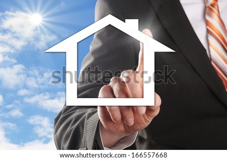 man chooses his dream house in front of the blue sky - stock photo