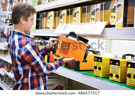 Man chooses welding machine in the store