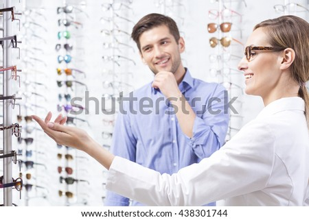 Man choosing a new pair of glasses at an optometrist - stock photo