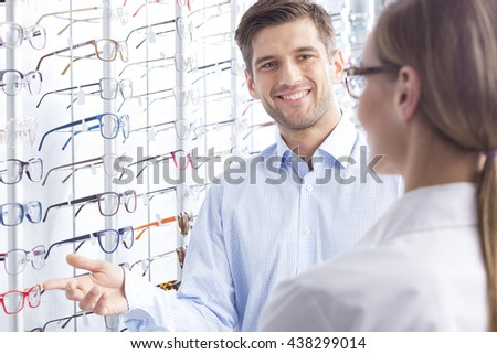 Man choosing a new pair of glasses at optician store