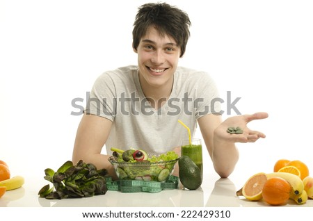 Man choosing between eating healthy organic food and pills. Happy man having a table full of organic food,juices and smoothie. Eating green food and taking spirulina pills - stock photo