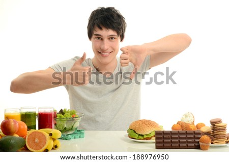 Man choosing between fruits, smoothie and organic healthy food against sweets, sugar, lots of candies and a big hamburger, unhealthy food - stock photo