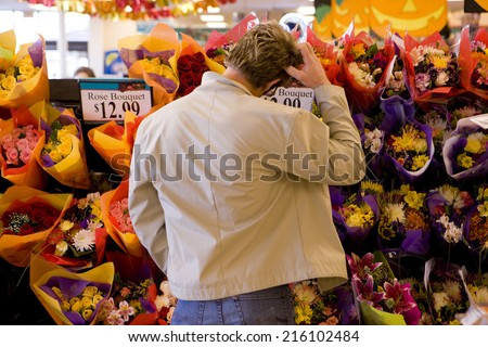 Man choosing bouquet of fresh flowers in grocery store - stock photo