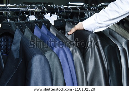 Man choosing business jacket from the raw in the shop. - stock photo