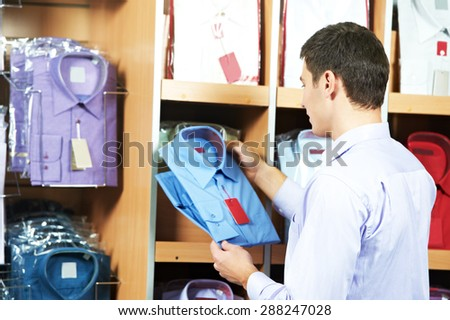 man choosing shirt during shopping at garments clothing shop - stock photo