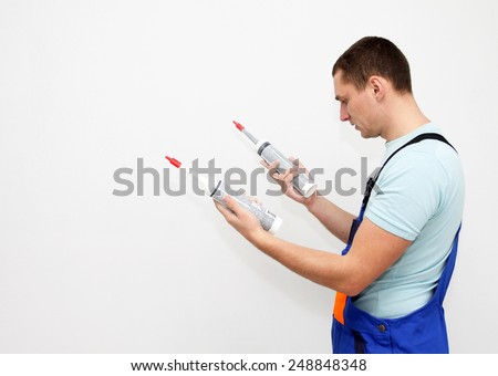 Man choosing silicone sealant - stock photo