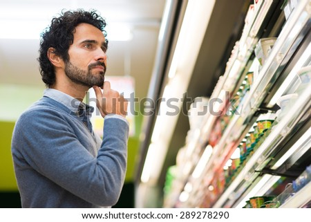 Man choosing the right product in a supermarket - stock photo