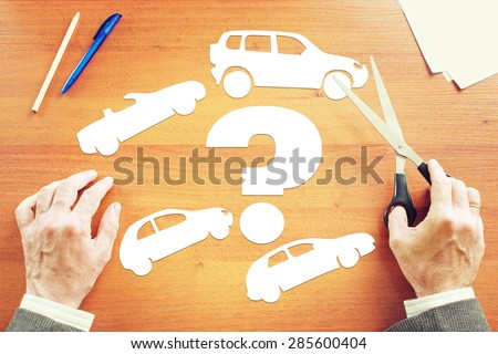 Man choosing which kind of car to buy. Abstract conceptual image - stock photo