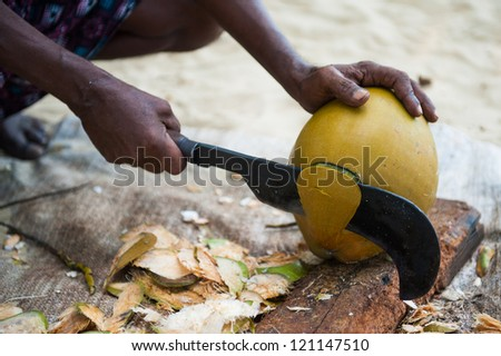Man chopping a fresh coconut in India - stock photo