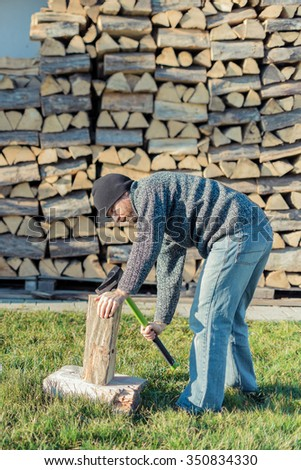 Man chopping a log of wood, stack of wood in background chopping a log of wood, stack of wood in background
