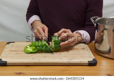 Man chopping green bell pepper  - stock photo