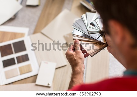Man chosing the right flooring for his house/appartement - stock photo