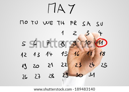 Man circling the date of 11th May with a red marker pen on a hand-drawn calendar for the month of May on a virtual interface to remind him that it is Mothers Day to commemorate mothers and motherhood - stock photo
