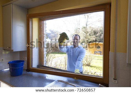 man cleaning a window at home. spring cleaning. - stock photo