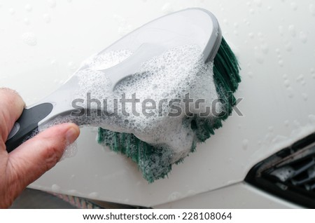 Man cleaning car bonnet with soapy brush
