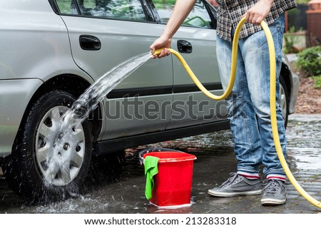 Man cleaning car in front of house - stock photo