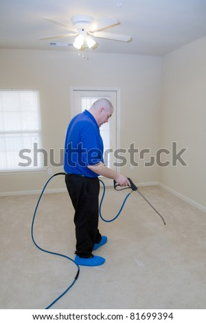 Man cleaning carpet with commercial cleaning equipment, during a pre-treat for stain removal