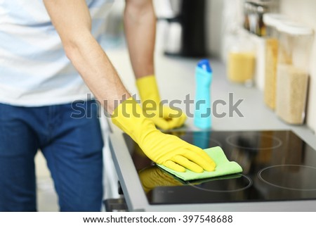 Man cleaning electric hob with spray and rag - stock photo