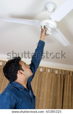 man cleaning fan at home - stock photo
