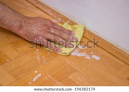 Man cleaning floor after painting wall with roller.  Selective focus.  - stock photo