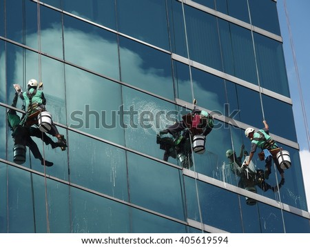 man cleaning glass building by rope access at height
