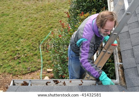 Man cleaning gutters on ladder - stock photo