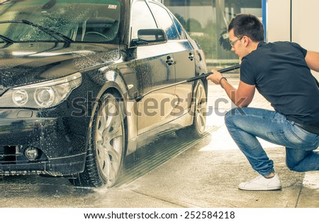 Man cleaning his car with soap and water - stock photo