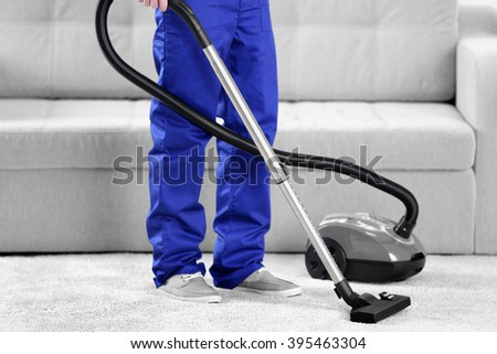 Man cleaning in the flat with vacuum cleaner - stock photo