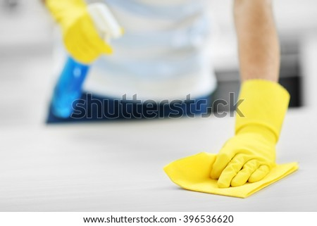 Man cleaning kitchen with spray and rag - stock photo