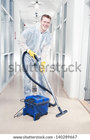 Man cleaning office with vacuum wearing protective overalls