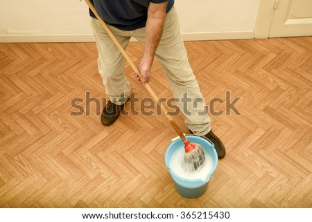Man cleaning parquet floor - stock photo