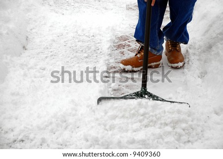 Man cleaning snow from a walkway with copy space - stock photo