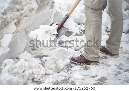 Man cleaning the snow with a shovel - stock photo