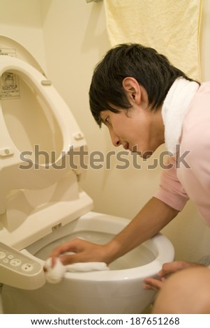 man cleaning toilet - stock photo